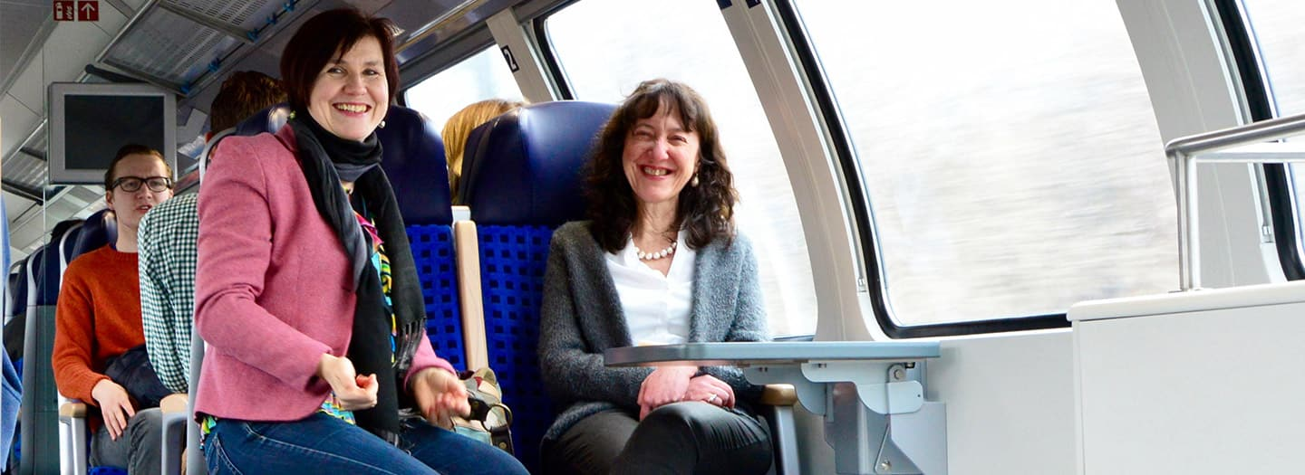 Two faculty smile from seats on a train